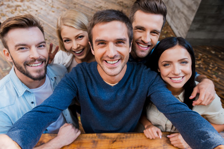 insanlar: Arkadaşlarınızla Komik selfie. Beş neşeli gençler selfie yapmak ve açık havada ayakta iken gülümseyen üstten görünümü