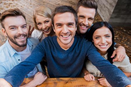 människor: Rolig selfie med vänner. Uppifrån av fem glada ungdomar gör selfie och ler samtidigt som står utomhus Stockfoto