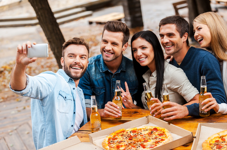pizza: ¡Hora de hacerse un selfie! Grupo de jóvenes alegres unión entre sí y haciendo selfie en el teléfono inteligente, mientras que beber cerveza y comiendo pizza juntos