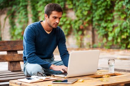 using the computer: Negocios en el aire fresco. Hombre joven confidente que trabaja en la computadora port�til mientras est� sentado en la mesa de madera al aire libre Foto de archivo