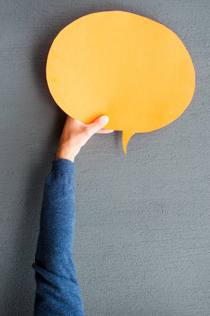 speech bubble: Speech bubble. Close-up of man stretching out empty speech bubble against grey background