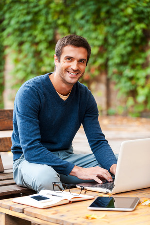 only adult: Face of job satisfaction. Smiling young man working on laptop and looking at camera while sitting at the wooden table outdoors Stock Photo