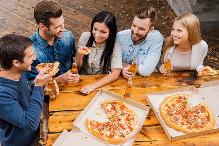 drinks on bar: Carefree time with friends. Top view of five cheerful peopleholding bottles with beer and eating pizza while standing outdoors