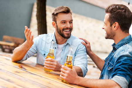 men talking: Beer time. Two cheerful young men talking to each other and holding bottles with beer while standing outdoors Stock Photo