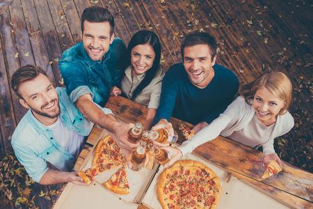 Celebrando ese día. Vista superior de cinco jóvenes felices que tintinean los vidrios con la cerveza y mirando a la cámara mientras está de pie al aire libre