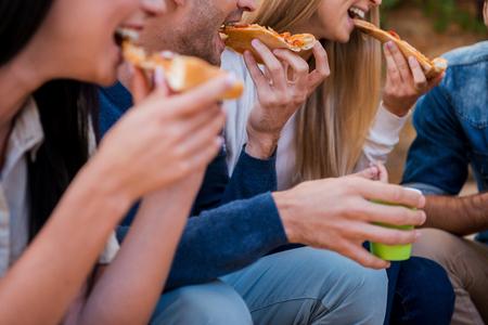 Tempo per la pizza! Gruppo di giovani a mangiare pizza mentre seduta all'aperto Archivio Fotografico - 45229507