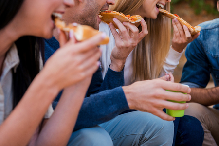 Time for pizza! Group of young people eating pizza while sitting outdoors Standard-Bild