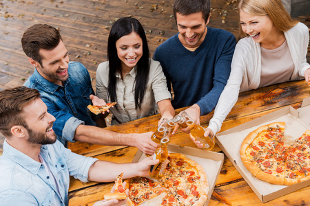 people eating: Finally it is Friday! Top view of five joyful young people clinking glasses with beer and eating pizza while standing outdoors