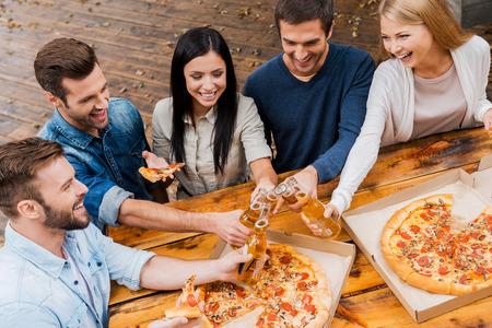 personas comiendo: Por último, es viernes! Vista superior de cinco jóvenes alegres tintineo vasos con cerveza y comiendo pizza mientras está de pie al aire libre