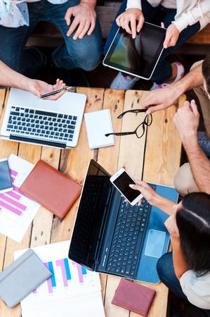 ludzie: Kreatywność w działaniu. Widok z góry czterech młodych ludzi, pracujących razem, siedząc na drewnianym stole Zdjęcie Seryjne