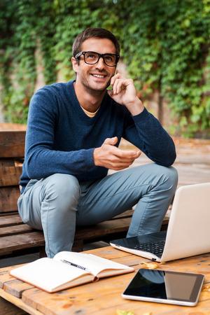 hombres jovenes: Bueno hablar de negocios. Feliz el hombre joven hablando por phonewhile móvil que se sienta en la mesa de madera al aire libre