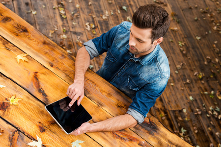 work table: Enjoying his work outdoors. Top view of confident young man working on digital tablet while sitting at the wooden table outdoors