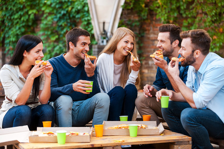 Enjoying pizza together. Group of happy young people eating pizza while sitting outdoors
