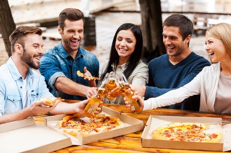 personas comiendo: ¡Salud! Grupo de jóvenes alegres comiendo pizza y aplaudir con cerveza mientras está de pie al aire libre