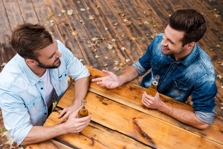 men talking: Enjoying beer with friend. Top view of two smiling young men drinking beer and talking to each other while standing outdoors
