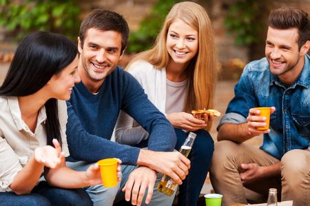 personas hablando: Compartiendo las últimas noticias. Grupo de jóvenes felices hablando el uno al otro y beber mientras está sentado al aire libre