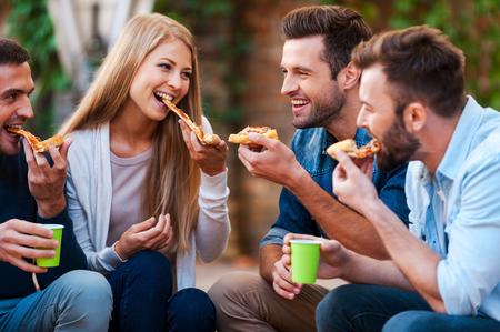 comiendo: Tan sabroso! Grupo de jóvenes alegres sonriendo y comiendo pizza mientras sentado al aire libre