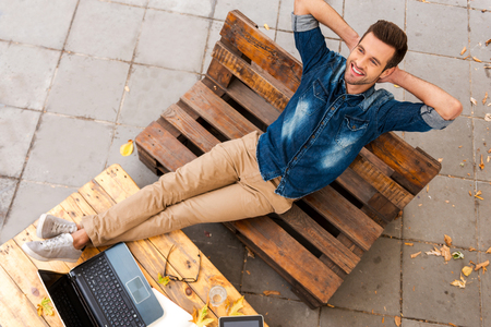 persona sentada: El aire fresco y de buen humor. Vista superior del hombre joven alegre sosteniendo la cabeza en la mano y sonriendo mientras se relaja al aire libre
