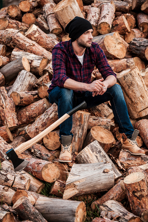 forester: Taking smoking pause. Full length of pensive young forester smoking and looking away while sitting on logs Stock Photo