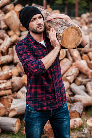 forester: Strong and confident. Serious young forester carrying huge log on his shoulder and looking away while standing outdoors Stock Photo