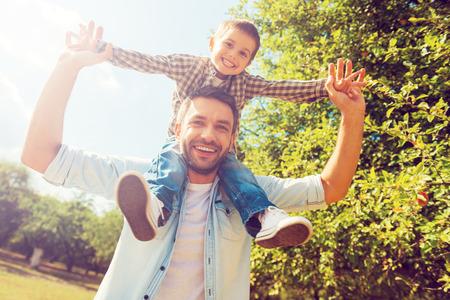 pequeño: Nos gusta pasar tiempo juntos! Ángulo de visión baja de niño feliz estirando las manos mientras su padre lo llevaba sobre los hombros