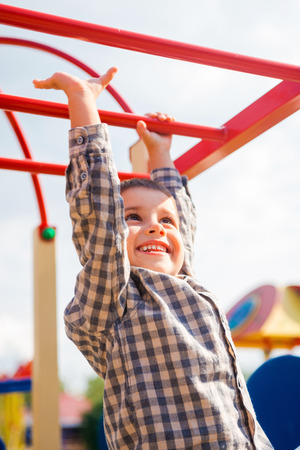 jungle gym: I can do it! Playful little boy expressing positivity while having fun on jungle gym