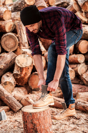 forester: Getting ready to work. Full length of confident young forester adjusting his shoes while leaning at the log Stock Photo
