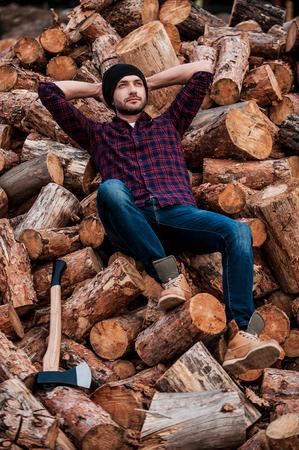 trabajando duro: Relajarse después de duro día de trabajo. Longitud total de forestal confía en los jóvenes que sostiene la cabeza con las manos y mirando hacia arriba mientras se apoya en los registros Foto de archivo