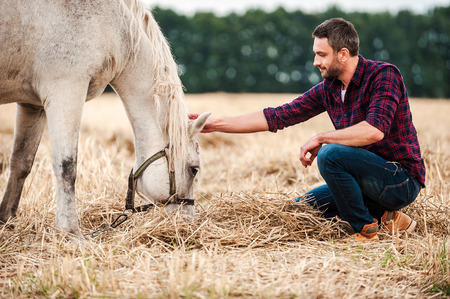 young farmer: His best friend. Side view of young farmer touching horse while sitting outdoors