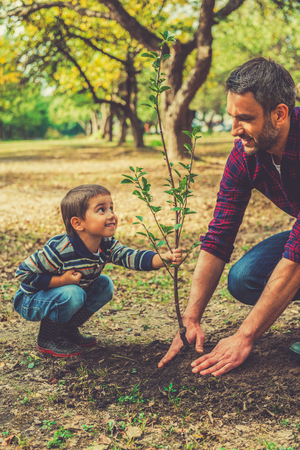 This tree will grow with you! Playful little boy helping his father to plant the tree while working together in the garden Stock Photo
