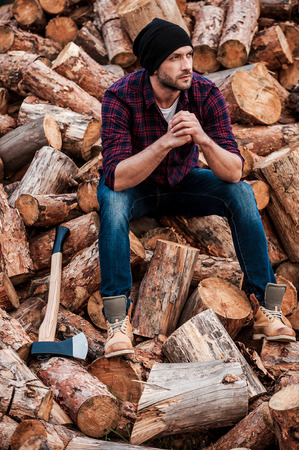 forester: After hard physical work. Full length of thoughtful young forester keeping hands clasped and looking away while sitting on logs Stock Photo