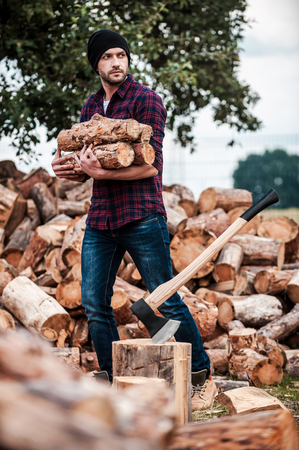 forester: Lumberjack at work. Handsome young forester holding logs and looking away while standing outdoors Stock Photo