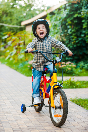 mouth opened: Cycling with fun. Joyful little boy keeping mouth opened and expressing positivity while riding on bicycle Stock Photo
