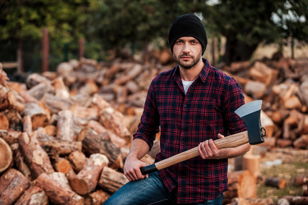 masculinity: Portrait of masculinity. Confident young forester holding axe and looking at camera while standing outdoors