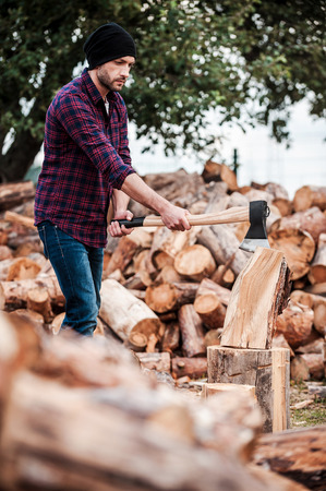 forester: Confident woodworker. Serious young forester cutting log while standing outdoors Stock Photo