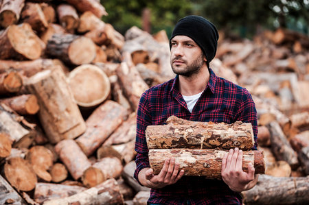 forester: Enjoying his work with wood. Confident young forester holding logs and looking away while standing outdoors