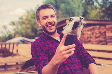 zoologico: Selfie con llama. Alegre joven haciendo selfie con la llama en su tel�fono inteligente mientras est� de pie en el zool�gico