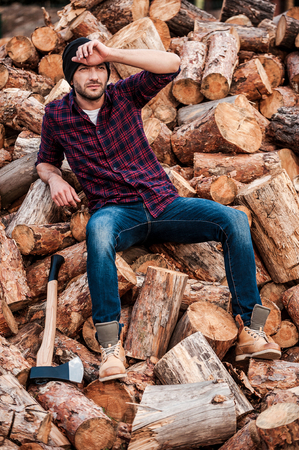 forester: Tired after hard work. Full length of tired young forester touching his forehead while sitting on logs