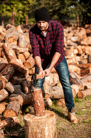 forester: Skilled forester. Full length of confident young forester cutting log while standing outdoors Stock Photo