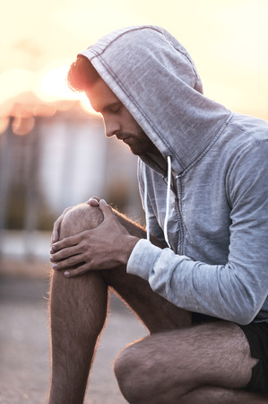 masaje deportivo: El masaje de la rodilla lesionada. Vista lateral del hombre joven que da masajes a la rodilla mientras est� sentado al aire libre