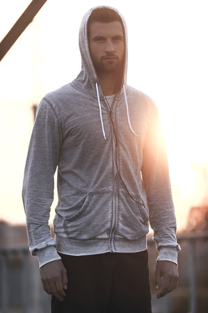 sportsman: Confiado y guapo. Hombre joven confidente en ropa deportiva mirando a la cámara mientras está de pie al aire libre
