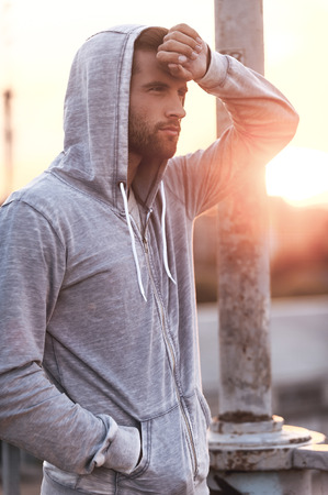 sportsmen: It was intense workout. Side view of tired young man touching his forehead while standing outdoors Stock Photo