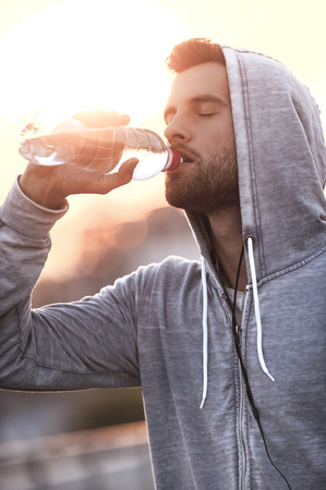 sportsmen: Staying hydrated. Confident young man drinking water while standing outdoors Stock Photo