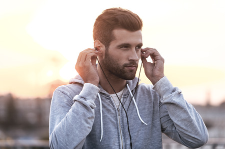 Music is always with me. Confident young man putting headphones into his ears and looking away while standing outdoors Stock Photo