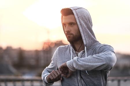 deportistas: Hacer ejercicio de aire fresco. Seguro de joven que estira su cuerpo antes de ejecutar mientras está de pie al aire libre