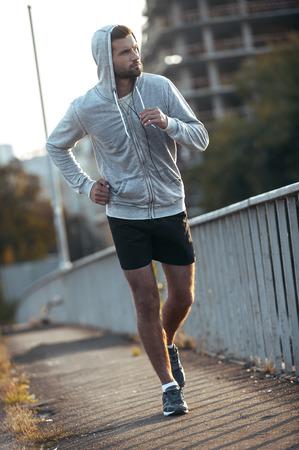sportsman: Sólo seguir corriendo! Longitud total de hombre joven y guapo mirando a otro lado mientras se ejecuta a lo largo de la carretera