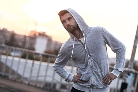 estiramiento: Capacitación en el aire fresco. Apuesto joven haciendo ejercicios de estiramiento antes de correr, mientras que defiende al aire libre