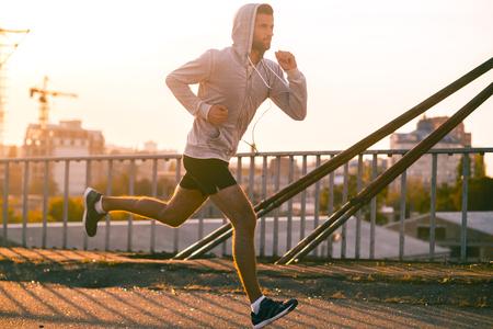 confianza: Mudarse a su meta. Vista lateral del hombre joven confidente que recorre el puente