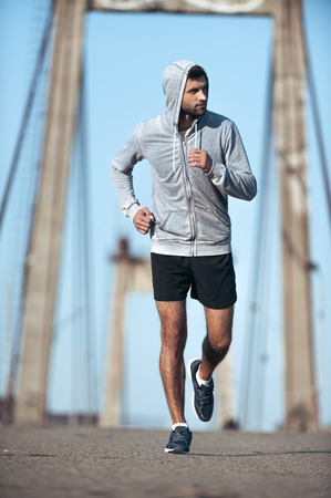 men running: Finding inspiration in his training. Full length of confident young man looking away while running along the bridge