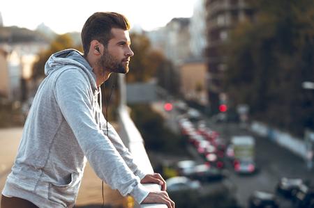 Enamorado de su ciudad. Vista lateral del hombre joven pensativo en los auriculares mirando a otro lado mientras está de pie en el puente